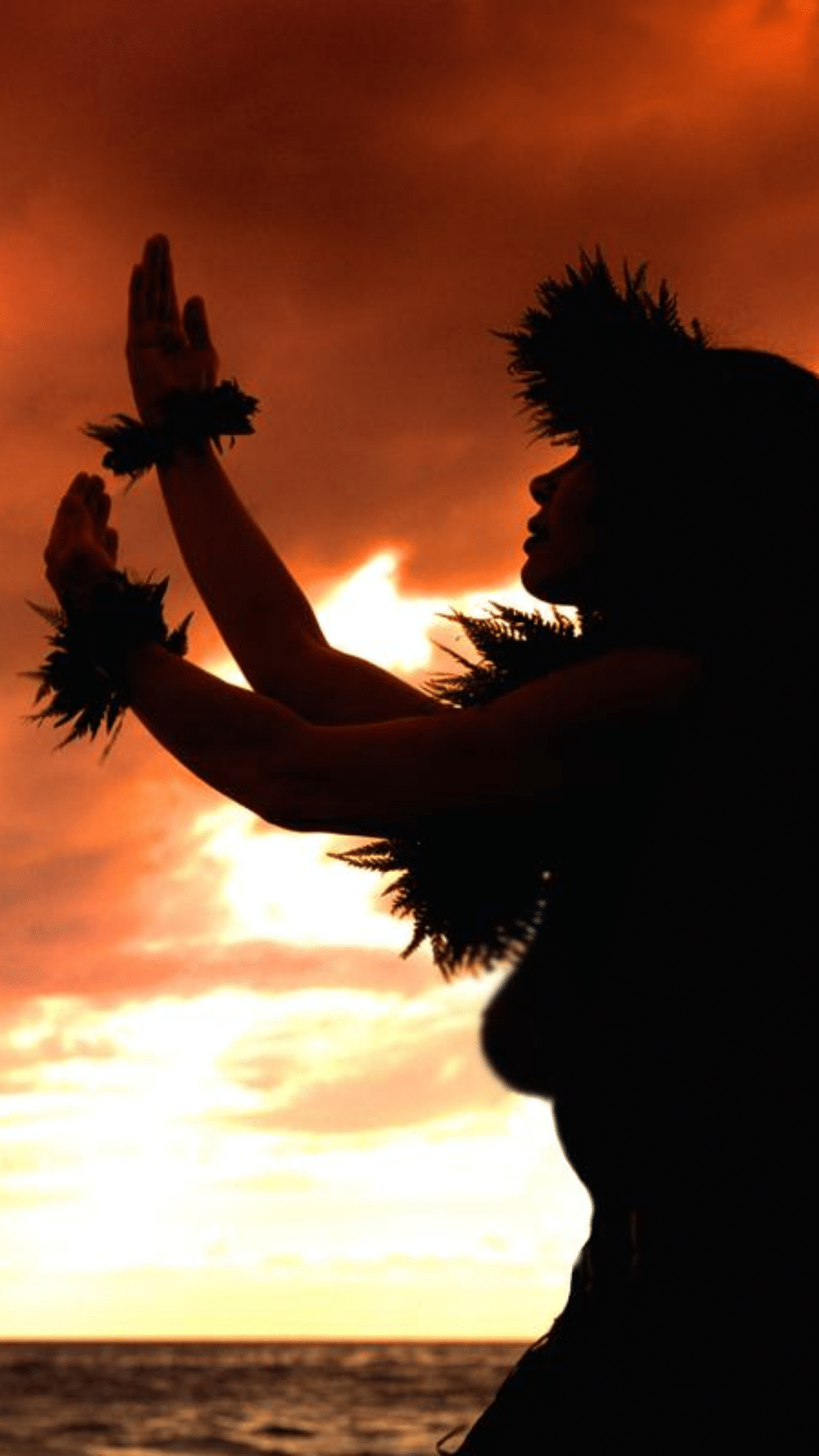Young woman dances the hula at sunset